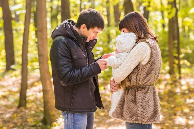 Jeune famille avec leur nouveau-né passe du temps en plein air dans le parc en automne.