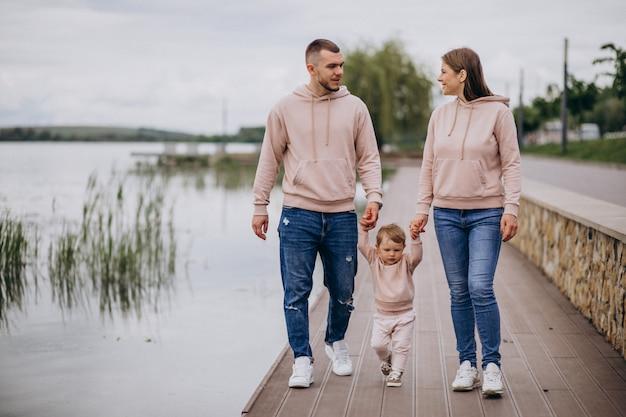 Jeune famille avec leur petit bébé dans un parc au bord du lac