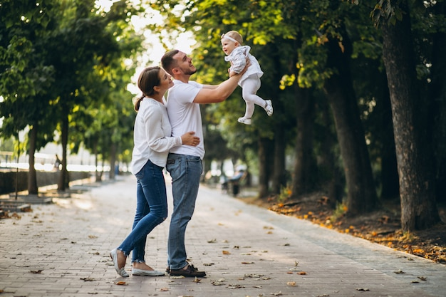 Jeune famille avec leur petite fille en automne parc