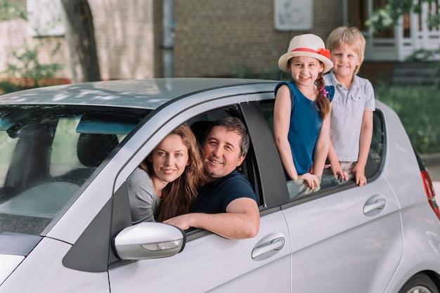 Jeune famille avec leurs enfants dans une voiture familiale.
