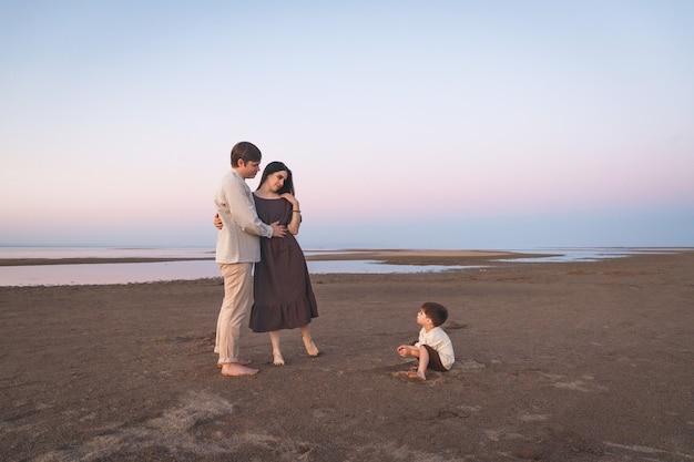 Une jeune famille en lin avec un fils de 3 ans marche le long de la plage sauvage du soir