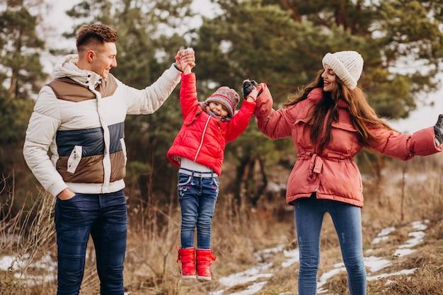 Jeune famille marchant ensemble dans la forêt à l'heure d'hiver