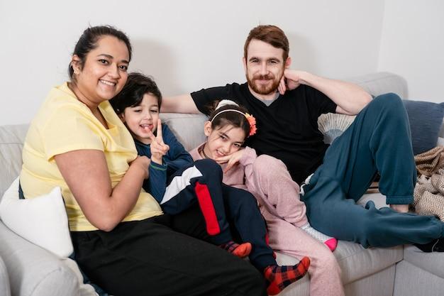 Jeune famille métisse s'amuser et se détendre au canapé. la vraie vie, les vraies personnes, la diversité