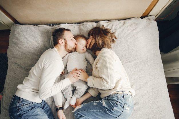 Jeune famille mignonne avec votre petit fils jouant à la maison sur le lit