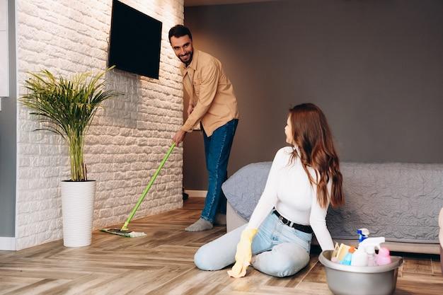 Jeune famille nettoyant leur appartement
