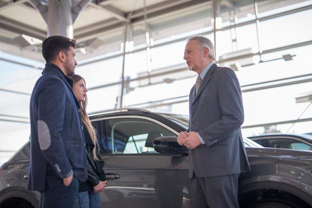 Jeune famille parlant au vendeur et choisissant sa nouvelle voiture dans une salle d'exposition