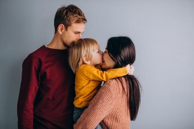 Jeune famille avec petit fils ensemble sur gris