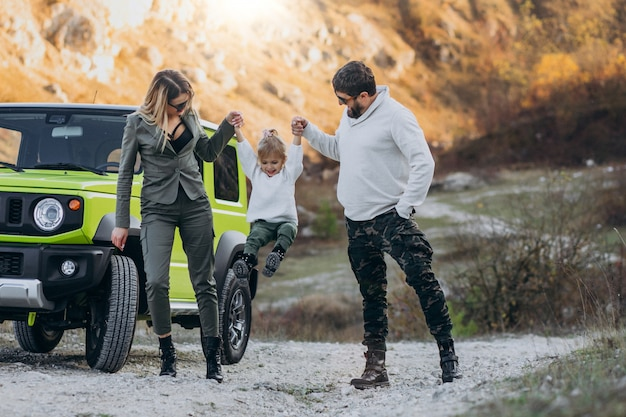 Jeune famille avec petite fille arrêtée en forêt