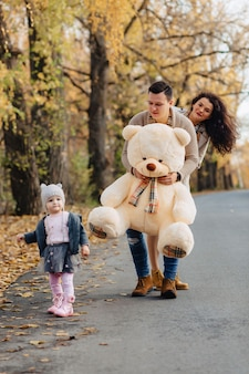 Jeune famille avec une petite fille au parc d'automne présente un gros ours