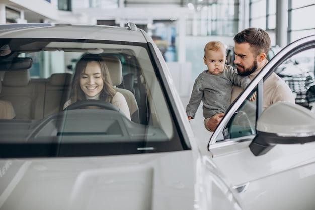 Jeune famille avec petite fille choisissant une voiture