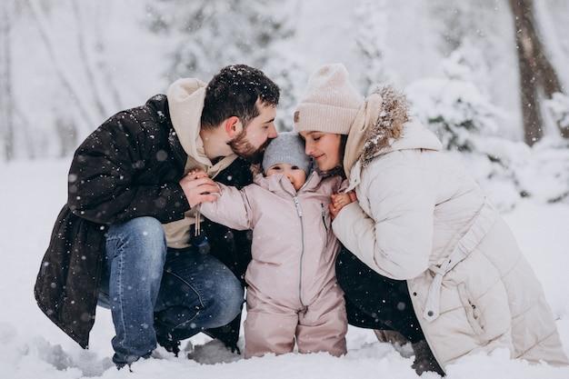 Jeune famille avec petite fille dans une forêt d'hiver pleine de neige