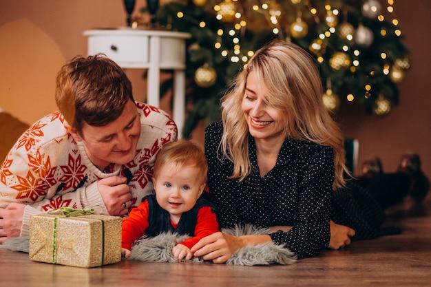 Jeune famille avec petite fille tenant des cadeaux de noël