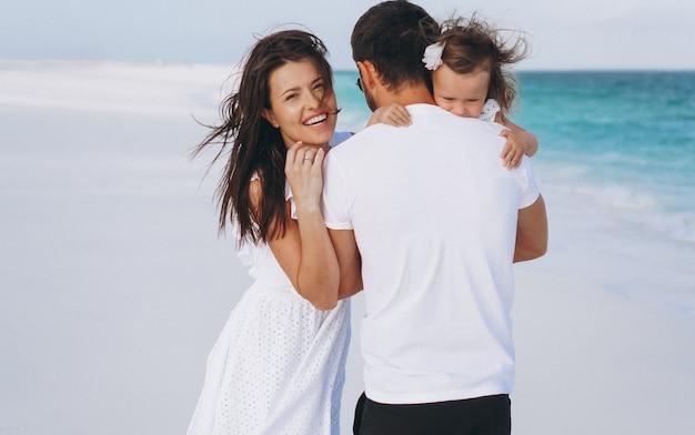 Jeune famille avec petite fille en vacances au bord de l'océan