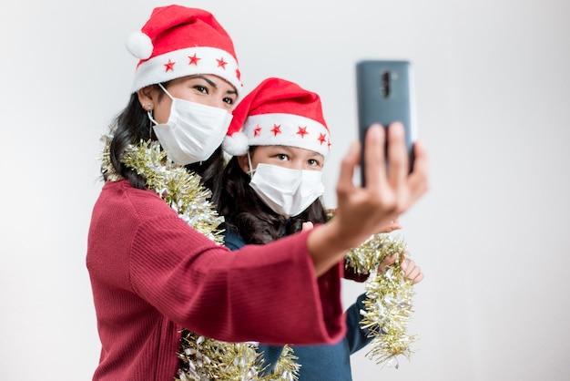 Jeune famille porte un chapeau de noël et un masque facial ayant un appel vidéo avec un téléphone intelligent.