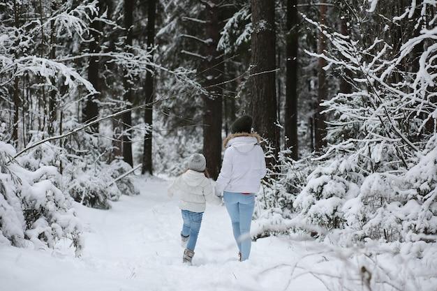 Jeune famille pour une promenade. maman et sa fille marchent dans un parc d'hiver.