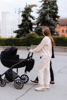 Une jeune famille avec une poussette pour bébé se promène dans la ville en été