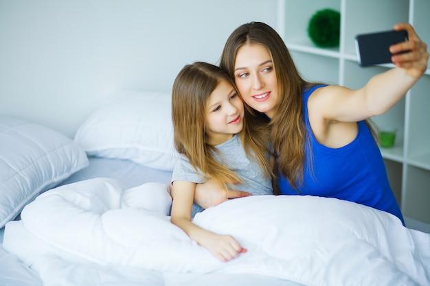 Jeune famille prenant selfie avec smartphone au lit