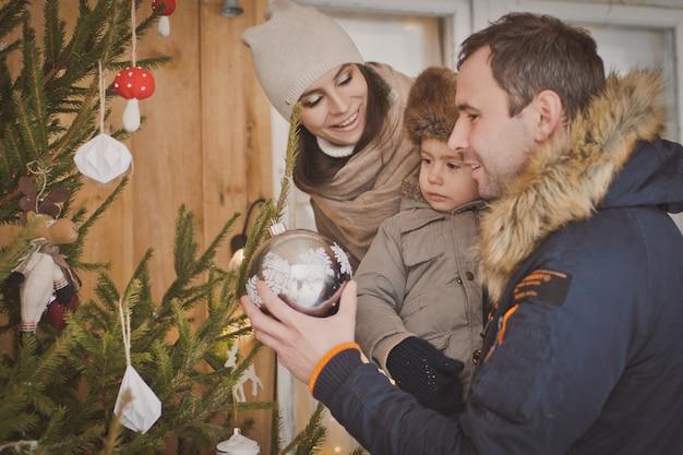 Jeune famille profitant de leur temps de vacances ensemble, décorer la guerre en plein air arbre de noël