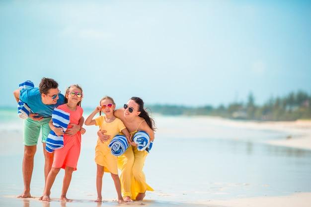 Jeune famille de quatre personnes en vacances à la plage