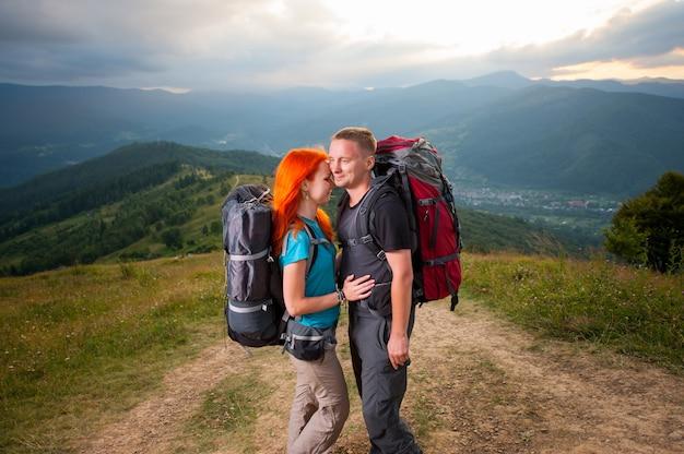 Jeune famille randonneurs debout face à face et souriant sur la route en montagne