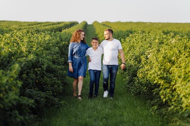 Jeune famille à la recherche en marchant dans le jardin