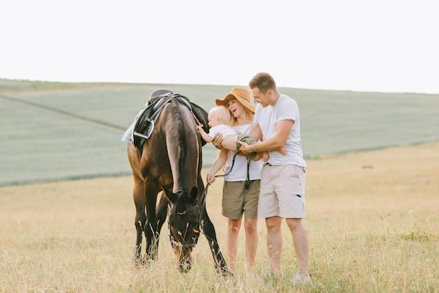 Une jeune famille s'amuse sur le terrain. parents et enfant avec un cheval