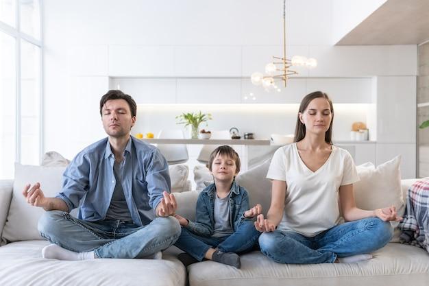 La jeune famille s'assied sur le sofa et médite