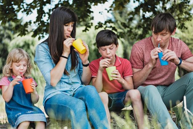 Jeune famille se détendre en plein air, boire du jus