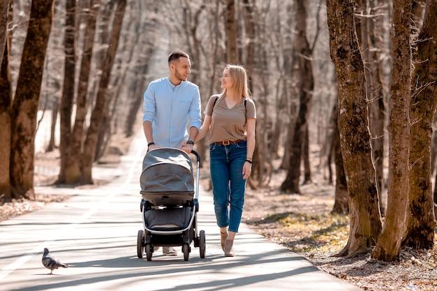 Jeune famille se promener dans le parc au printemps avec un enfant en bas âge dans une poussette. parents heureux