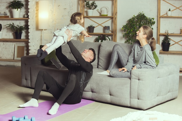 Jeune famille se reposant après avoir fait du yoga aérobie fitness à la maison mode de vie sportif devenir actif d...