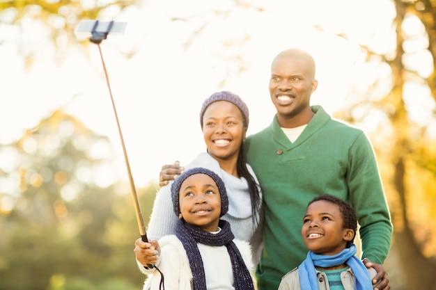 Jeune famille souriante prenant selfies