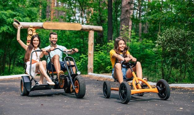 Jeune famille de touristes heureux moderne en vacances à vélo et amusez-vous ensemble