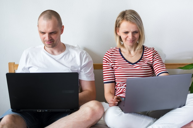 Jeune famille travaille à distance de la maison sur le lit à l'ordinateur. coronavirus en couple en quarantaine. restez à la maison en toute sécurité. enseignement à distance, éducation et travail. commander des produits alimentaires en ligne
