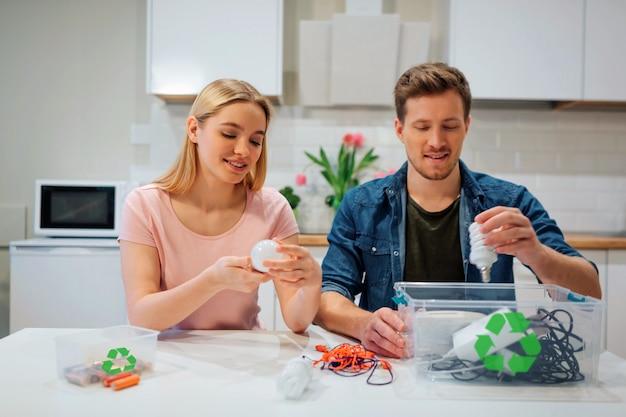 Jeune famille triant des ampoules, des piles et d'autres déchets électroniques dans des conteneurs