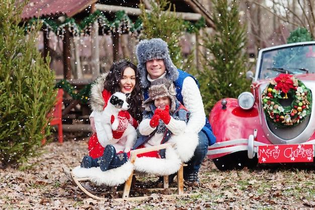 Jeune famille de trois personnes posant avec chiot husky contre la voiture de noël rouge dans la forêt.