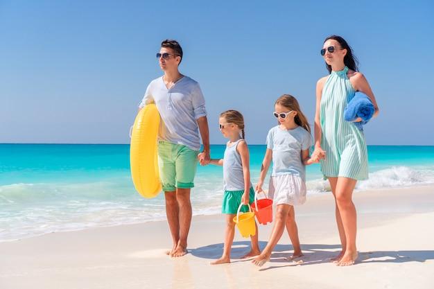 Jeune famille en vacances s'amuser sur la plage