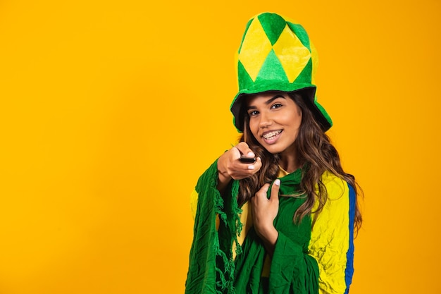 Jeune fan girl brésilienne avec manette en main prête à regarder le match brésilien