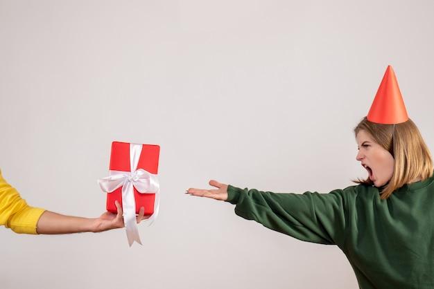 Jeune femme acceptant présent de mâle sur blanc