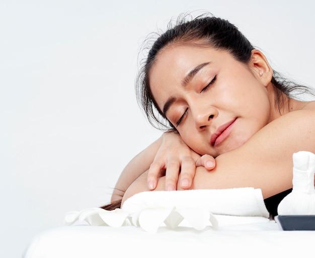 Jeune femme et accessoires de spa sur table de massage