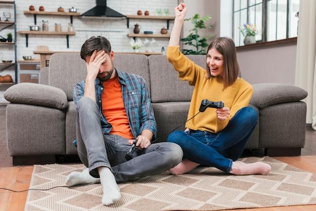 Jeune femme acclamant après avoir remporté le jeu vidéo avec son mari