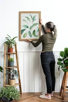 Jeune femme accrochant un cadre de peinture d'impression de feuille sur le mur