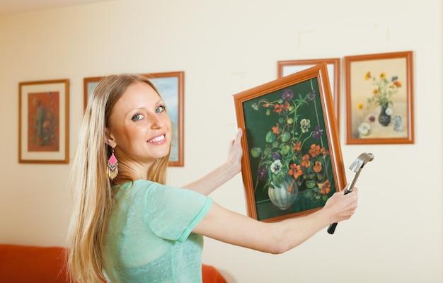Jeune femme accrochant l'image d'art