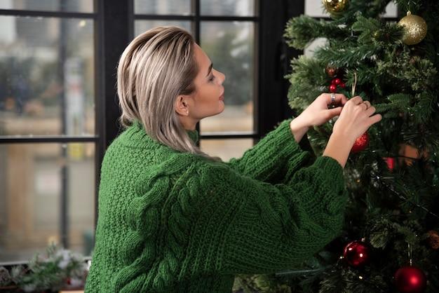 Une jeune femme accroche un jouet d'arbre de noël sur une branche d'un sapin
