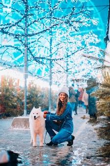 Jeune femme accroupie à côté d'un chien dans une rue d'hiver