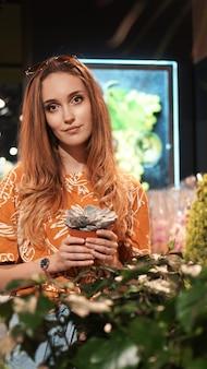 Jeune femme achetant des fleurs dans un pot dans un centre de jardinage