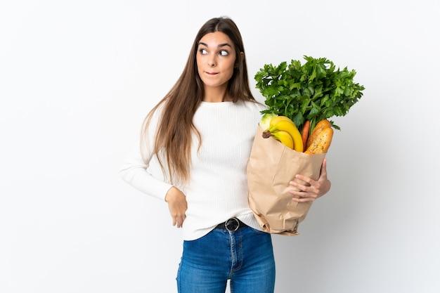 Jeune femme achetant de la nourriture isolée sur un mur blanc ayant des doutes et de la pensée