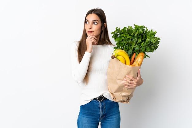 Jeune femme achetant de la nourriture isolée sur un mur blanc en pensant à une idée tout en regardant