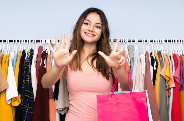 Jeune femme achetant des vêtements dans un magasin comptant sept avec les doigts
