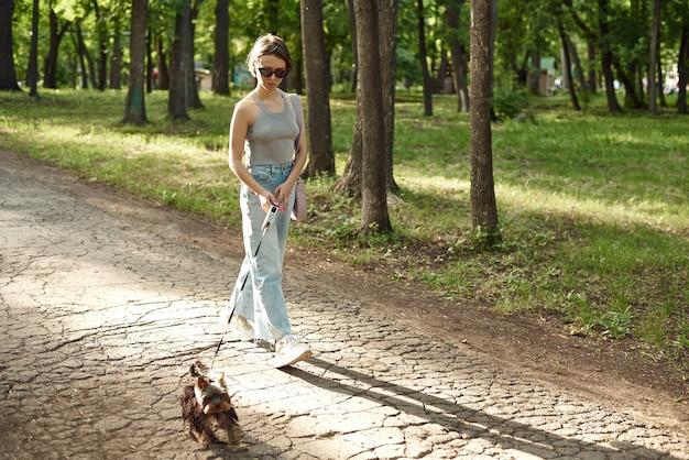 Jeune femme active avec un chien pour une promenade dans une belle nature d'été