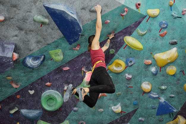 Jeune femme active dans des vêtements de sport suspendus sous le plafond tout en tenant par des poignées